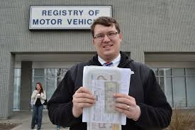 norton resident chris barrows of barrows insurance agency mansfield holds new plates and paperwork outside the taunton registry of motor vehicles friday