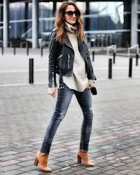 cedar atkins wears a belted leather jacket with a beige turtleneck sweater skinny denim jeans