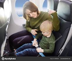 young mother helping her little son with safety belt during traveling by an airplane stock