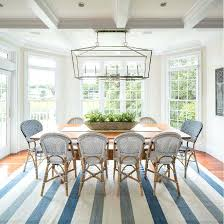 this coastal dining area features a linear chandelier from visual comfort and bistro chairs lily serena
