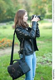 attractive young girl taking pictures outdoors cute teenage girl in blue jeans and black leather