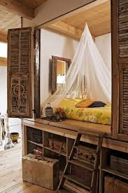 Rustic alcove bed with storage compartments underneath and a delicate canopy