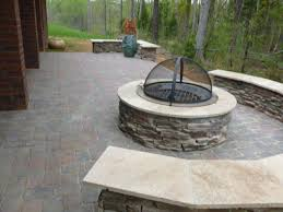 fieldstone outdoor fireplace paver patio with wood burning fire pit and cover on it and stone sitting wall