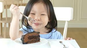 Asian girl eating a cake