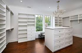 custom walk in closet with island chandelier and window with bench