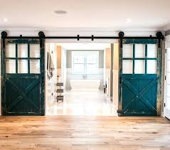 barn door with glass panels with wide planked hardwood floors alongside clad walls framing doorway highlighted