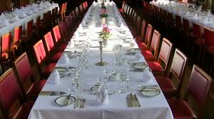 fine dining proper table service. place settings at a large formal dinner. the host and hostess may be seated fine dining proper table service r