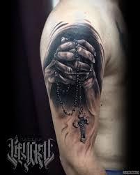 крест в руках молящегося тату на предплечье у парня добавлено