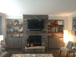 our beautiful reclaimed wood floating shelves flanking stone fireplace with grey base cabinets located in