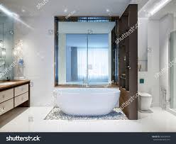 spacious all white bathroom. Spacious And Bright Modern Bathroom With White Tile, Large Mirror, Bathtub Pebbles On All R