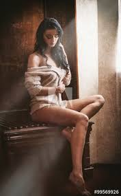 Attractive Sexy Brunette Half Naked Posing Provocatively In Window Frame Portrait Of Sensual Woman In Classic Boudoir Scene Woman With Long Hair Daydreaming And Enjoying The Bright Day Light Stock Photo