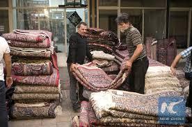 iranian workers arrange handwoven carpets at an old carpet bazaar in downtown tehran iran on july 22 2018 xinhua ahmad halabisaz