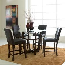 round glass top dining table with black wooden base and shelf added by four black leather chairs on brown rug