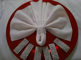 silver bling napkin ring with white napkin and red charger plate fan folded napkin with bling handle