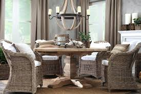 rattan dining chairs traditional round wooden dining table under decorative chandelier paired with comfortable rattan dining