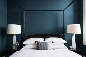 black canopy bed with deep blue romantic walls