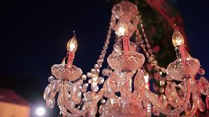 candle like glass crystal chandelier ceiling lights on the metal frame on the backgroung light of the latern and night sky romantic evening