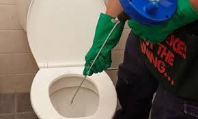 person unblocking the toilet using the auger