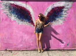 alexandra lapp in front of walls of los angeles the global angel wings wall