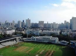 mumbai a grassy ground skyscrapers behind it