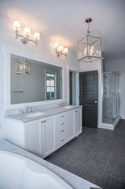 bathroom features gray shaker vanity: white and grey bathroom features a white shaker vanity topped with grey quartz under a full length vanity mirror lined with sconces atop a white ma